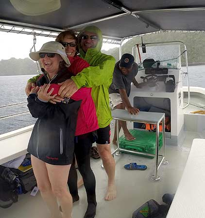 bentprop crew keeping warm on boat during rain shower in palau