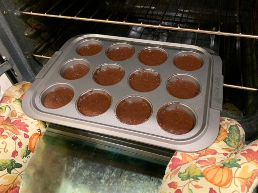 Double chocolate muffin mix in a muffin pan going into an oven