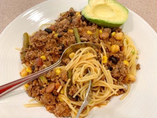 Meat sauce on a bed of spaghetti with an avocado on the side on a white plate