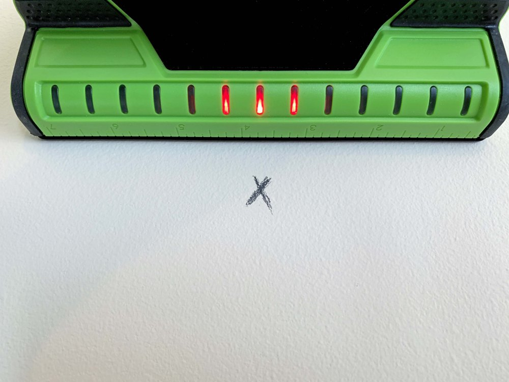 Green and black stud finder with red LED lights and a black X on a white wall
