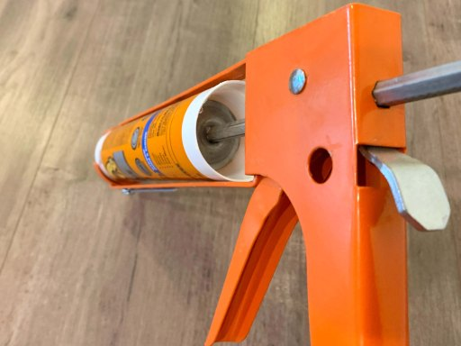 Bottle of caulk inserted into an orange caulk gun