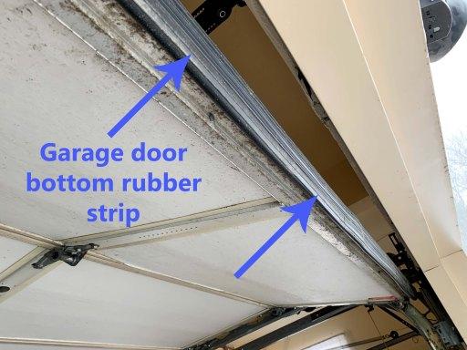 Opened garage door with garage door rubber bottom highlighted by blue arrows