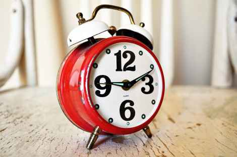 Red alarm clock with numbers and bells