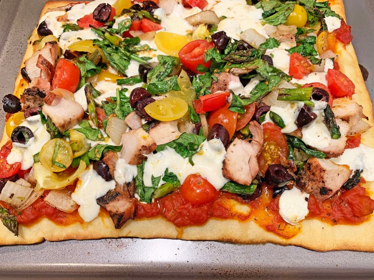 Cooked grilled chicken and veggie pizza on a pizza pan