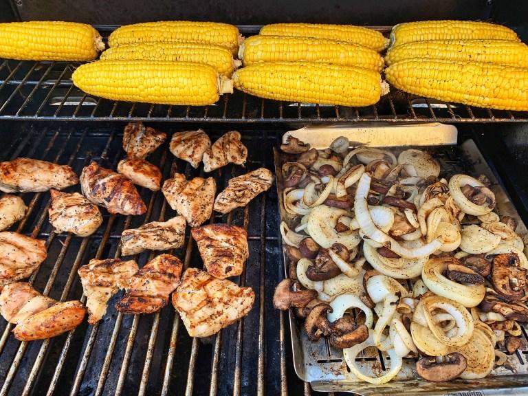 Corn, portobello mushrooms, onions, and chicken grilling on a barbecue