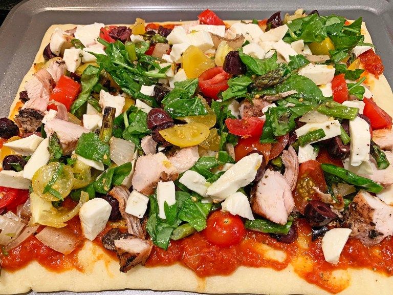Chicken and veggie toppings on top of pizza dough