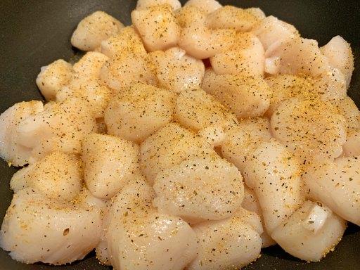 Seasoned sea scallops cooking in a black frying pan