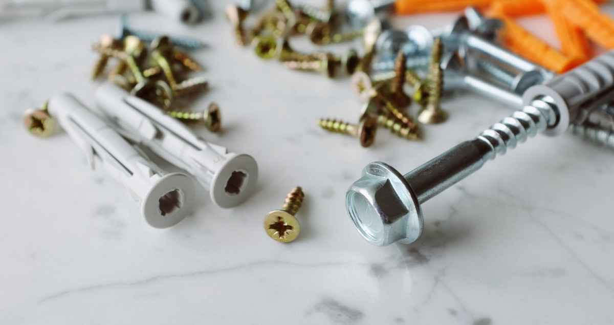 bunch of various screws and dowels of different sizes placed on marble table