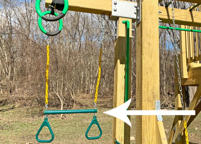 A green trapeze swing bar and rings on a playground