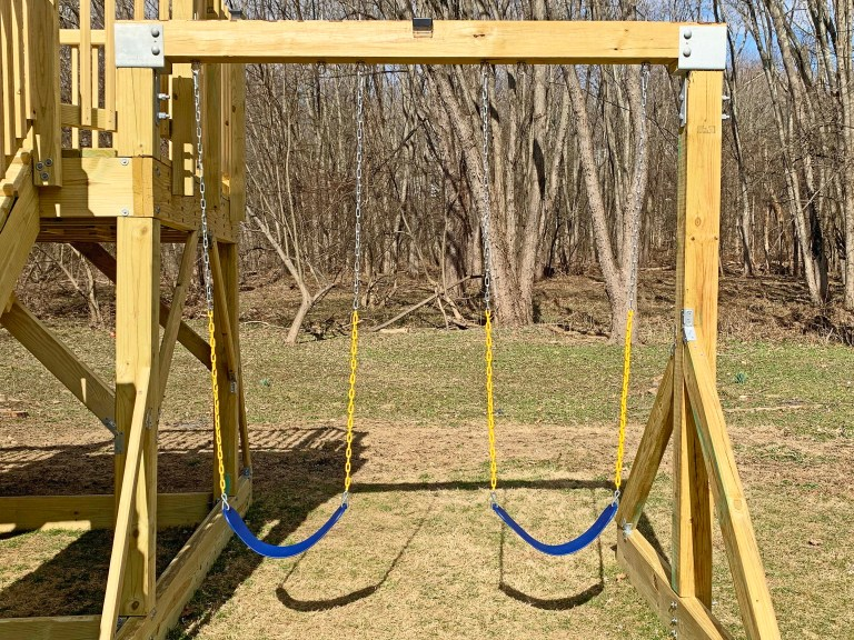 Two blue swings on a playground