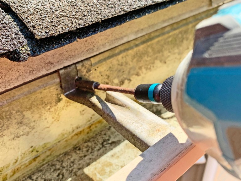 Fastening a gutter hanger with a screw and impact driver