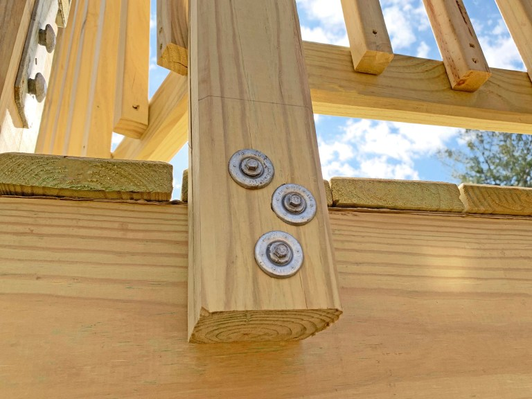 FastenMaster ThruLOK screw bolts secure a handrail post to a playground