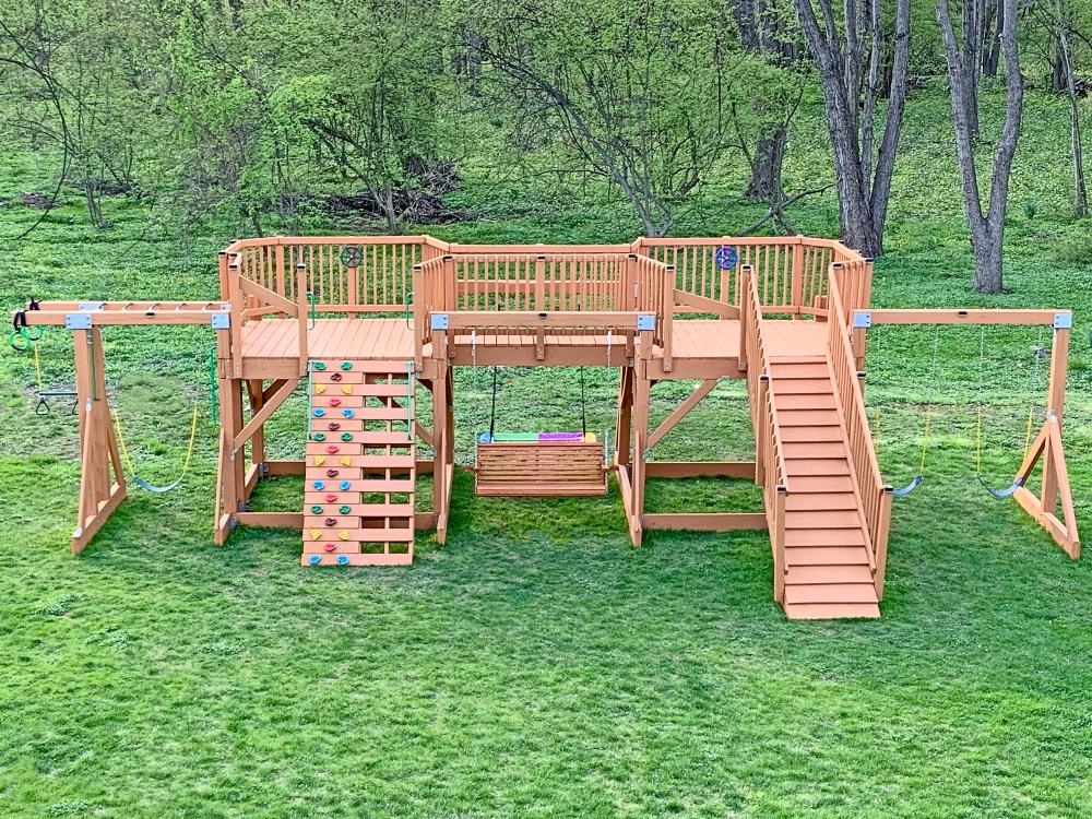 playground with swings and monkey bars, wood is stained
