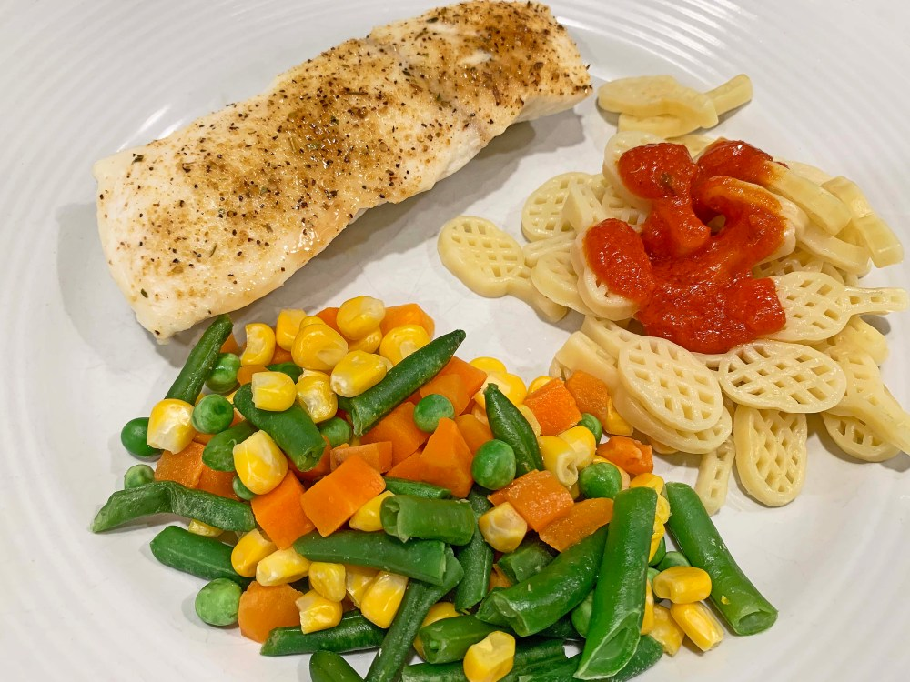 Piece of seasoned white fish, mixed vegetables, and pasta with red marinara sauce on a white plate.