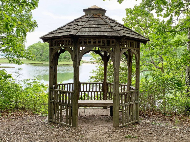 Wooden gazebo in a forest with water in the background