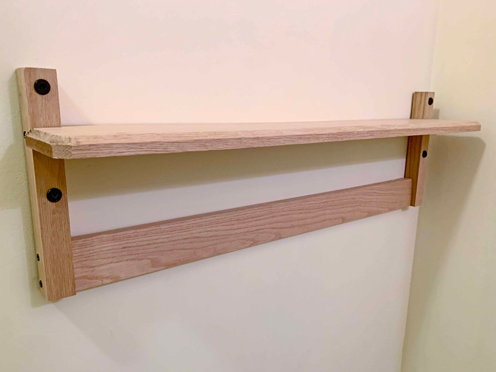 Light-colored wood with black screws on a white wall