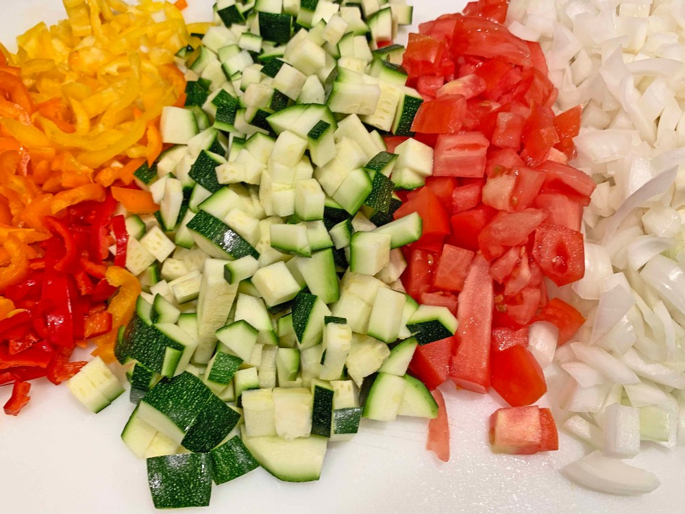 Diced red bell peppers, diced orange bell peppers, diced yellow bell peppers, diced red tomato, and diced white onion on a white cutting board