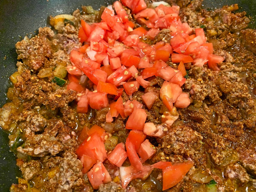 Brown ground beef and diced red tomato cooking in a black frying pan