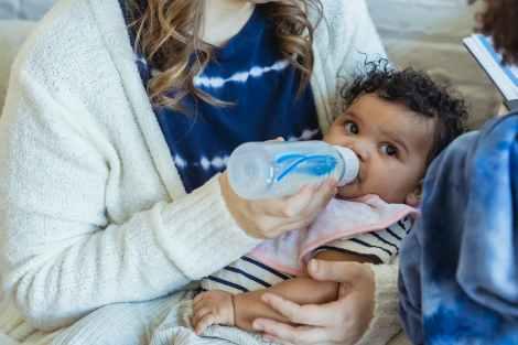mother feeding black baby from bottle