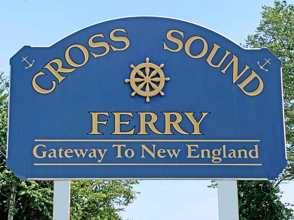 Blue sign with gold-colored letters with blue sky and green trees in background