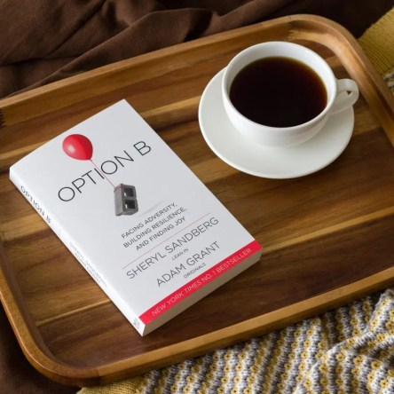"The book ""Option B"" and a cup of coffee on a tray"