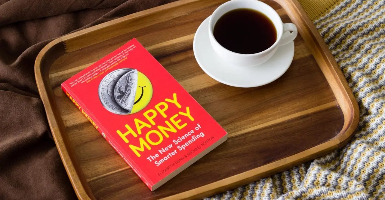 """The book """"Happy Money"""" and a cup of coffee on a tray"""