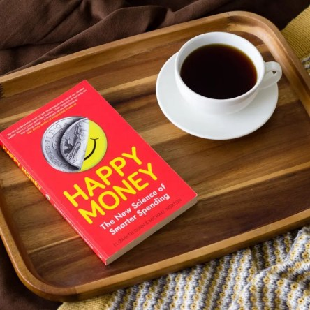 "The book ""Happy Money"" and a cup of coffee on a tray"