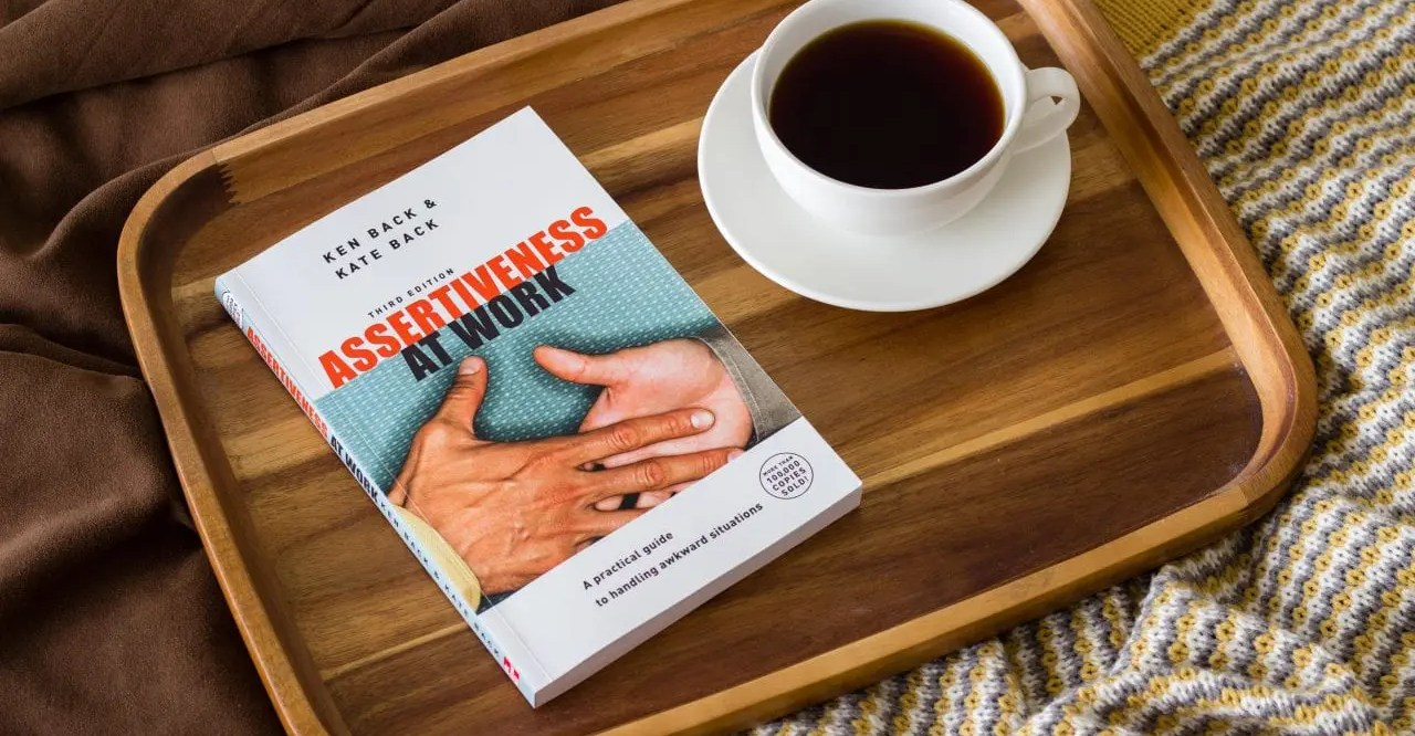 "The book ""Assertiveness at Work"" and a cup of coffee on a tray"