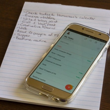 A paper notepad and a smartphone, both featuring to-do lists