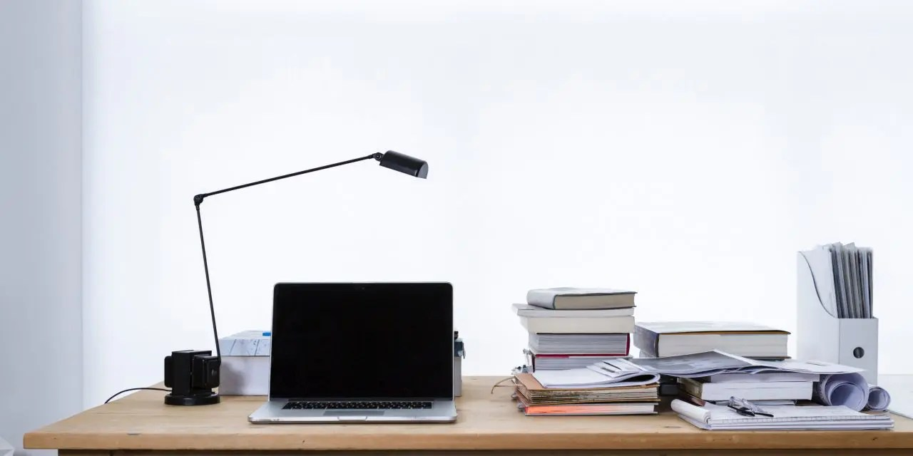 A laptop and several piles of paper and books on a wooden desk