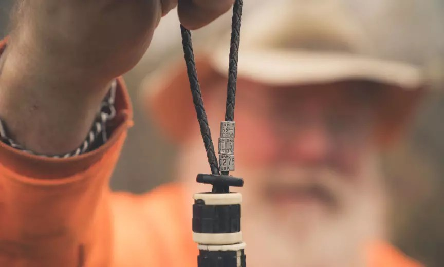 A bird hunter holds up woodcock bands.