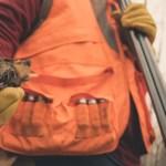 A bird hunter holds a woodcock and a shotgun