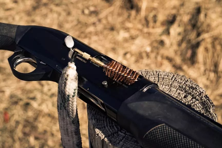 A bore snake being inserted into a shotgun barrel