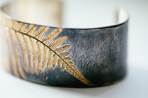 Wide cuff bracelet with gold fern