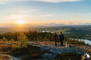 Två personer och en hund promenerar på Hällberget