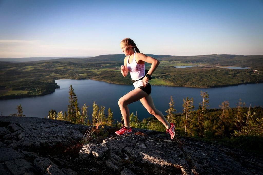 En flicka som löptränar och springer på ett berg