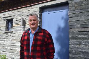 Dan Olofsson vid ett av husen i Kälapannsjön byggt i Offerdalsskiffer. Nu erbjuder han sig bistå folk som inte har ekonomiska resurser att driva långvariga och kostsamma domstolstvister mot Vattenfall i olika juridiska instanser, gällande den planerade vindkraftsinustrin i Nordbyn/Vallsta. Foto © Jämtlands Tidning.
