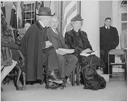 Photograph of Eleanor Roosevelt and the late President Roosevelt's dog, Fala, at the dedication of the Franklin D. Roosevelt home at Hyde Park, New York, 4/12/1946. (National Archives Identifier 199362)