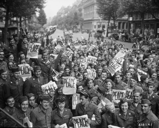 """American servicemen and women gather in front of """"Rainbow Corner"""" Red Cross club in Paris to celebrate the conditional surrender of the Japanese on August 15, 1945. (111-SC-210241)"""