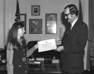 Adrienne Thomas receives an award from Archivist of the United States Bert Rhoads,11/30/1973. (Records of the National Archives)