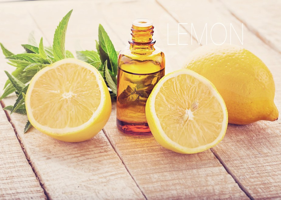 sliced lemons and peppermint leaves on a wooden table with a bottle of essential oil- Young Living