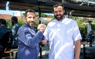 Na foto vemos à esquerda o chef Jean Christophe Burlaud e à direita o chef Marcelo Bastos, estão segurando na mão um do outro como sinal de conexão