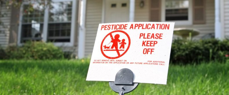 Pesticide application warning sign on lawn