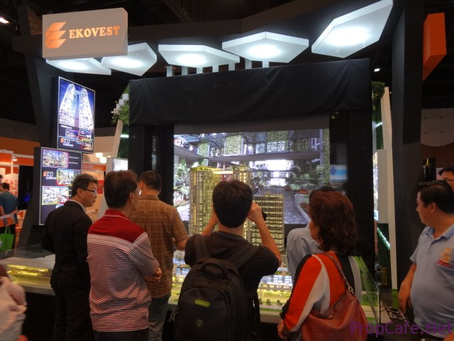 Crowd looking at the scale model and the display screen behind
