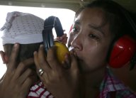 A mother cries in relief upon boarding a Philippine Air Force helicopter, Monday November 11, 2013 following Friday's typhoon Haiyan which lashed Guiuan township, Eastern Samar province, central Philippines. (Photo by Bullit Marquez/AP Photo)