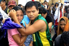 A husband and wife protect their baby from the rain as they wait for an evacuation flight in Tacloban, central Philippines, Tuesday, November 12, 2013. (Photo by Wally Santana/AP Photo)