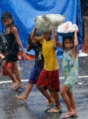 Survivors carry their belongings amidst heavy downpour after Typhoon Haiyan battered Tacloban city in central Philippines November 10, 2013. (Photo by Erik De Castro/Reuters)