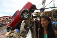 A woman pauses near a truck that was swept away by a typhoon in Tacloban, Philippines, Wednesday, November 13, 2013. Typhoon Haiyan, one of the strongest storms on record, slammed into six central Philippine islands on Friday leaving a wide swath of destruction. (Photo by Dita Alangkara/AP Photo)