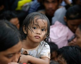 A child waits with fellow typhoon survivors as they line up in the hopes of boarding an evacuation flight on a C-130 military transport plane Tuesday, November 12, 2013, in Tacloban, central Philippines. (Photo by Bullit Marquez/AP Photo)