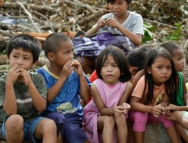 Children who say they fled when armed men were seen in their village eat bread while waiting in Tacloban city, Leyte province in central Philippines Wednesday, November 13, 2013. Five days after one of the strongest tropical storms on record leveled tens of thousands of houses in the central Philippines, relief operations were only starting to pick up pace, with two more airports in the region reopening, allowing for more aid flights. (Photo by Bullit Marquez/AP Photo)
